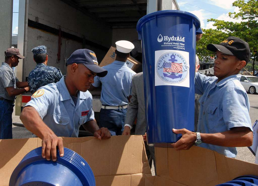 Members of the Dominican Republic defense forces load pallets of Project Handclasp humanitarian aid delivered by High Speed Vessel Swift (HSV 2).