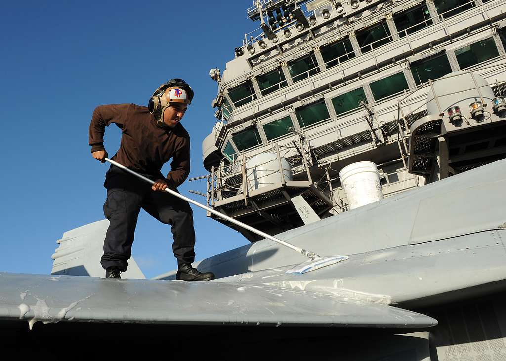 Sailor washes a jet aboard USS Abraham Lincoln.
