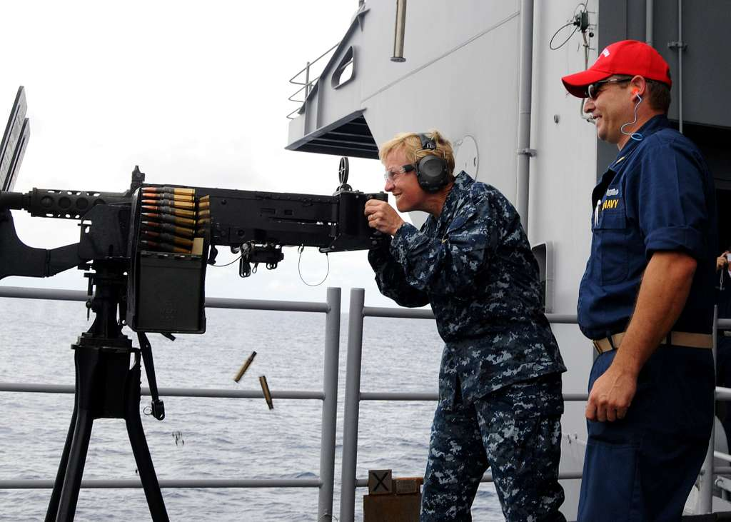 Rear Adm. Nora Tyson, commander of Carrier Strike Group (CSG) 2, fires a .50-caliber machine gun.