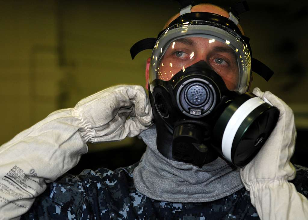 Yeoman Seaman Michael Barnes, assigned to the administration department of the aircraft carrier USS George H.W. Bush (CVN 77), dons a MCU-2P gas mask.