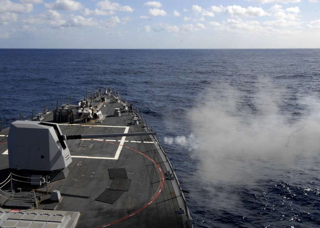 The guided-missile destroyer USS Bainbridge (DDG 96) fires a practice round from the MK-45 5-inch/54-caliber lightweight gun during routine training operations.