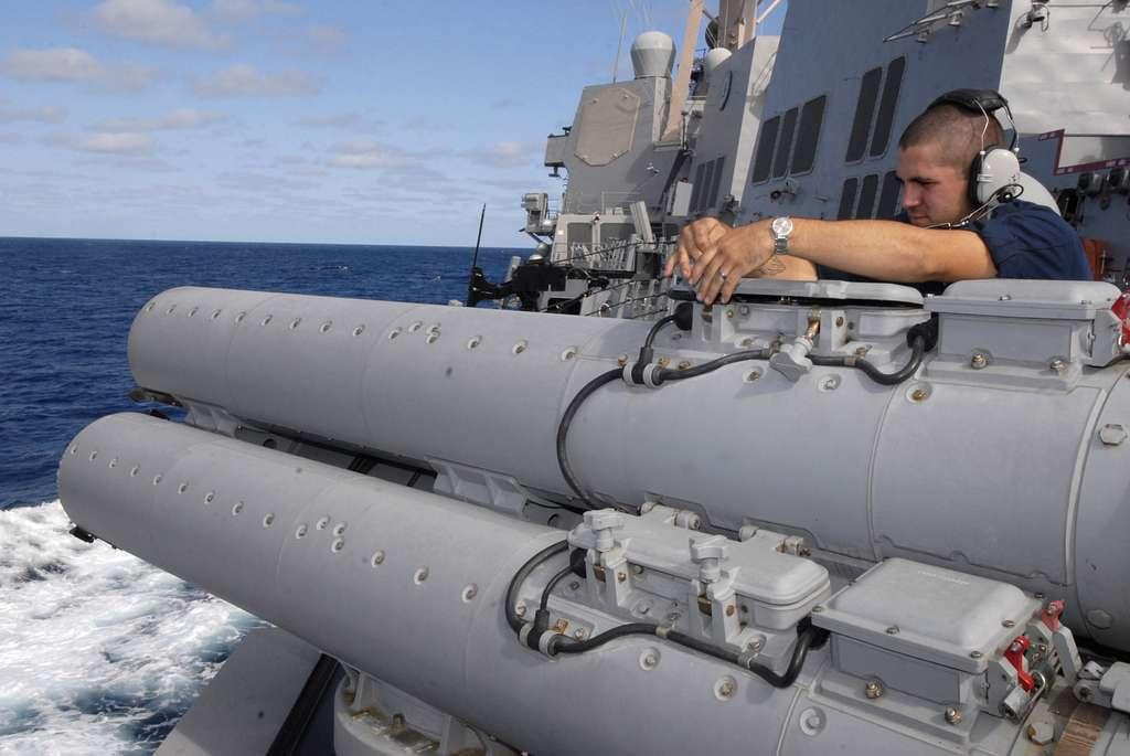 Gunner's Mate 3rd Class Brian Myers conducts maintenance on MK-32 torpedo tubes aboard USS Bainbridge (DDG 96).