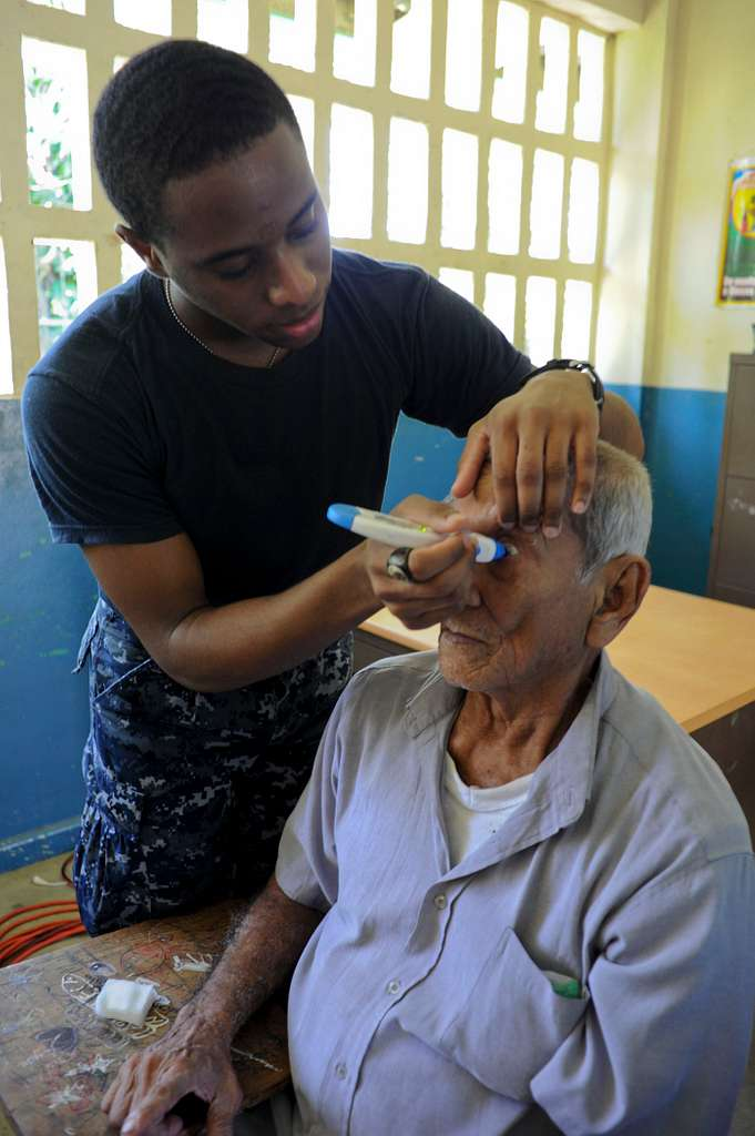 Hospital Corpsman Aaron London checks a man's eye pressure during a medical screening at a medical site in Panama.
