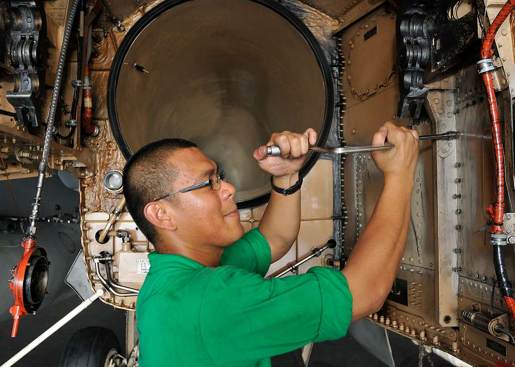 Aviation Structural Mechanic (Equipment) Airman Frederick Copuyoc removes bolts from the access panel of an F/A-18C Hornet during a scheduled maintenance.