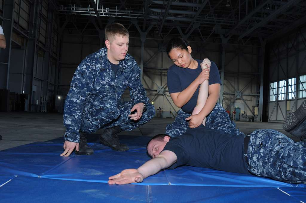 Master-at-Arms Seaman Chase Rardin, left, observes Culinary Specialist 3rd Class Ferose Pagarigan