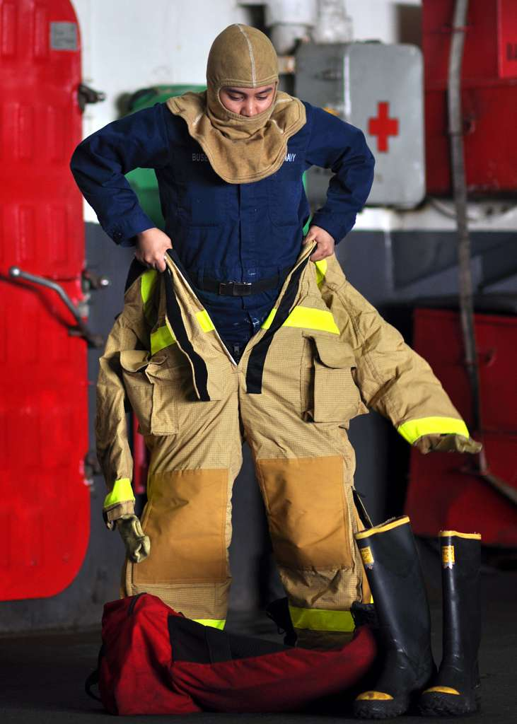 A Sailor dons firefighting coveralls during a mass casualty drill in the hangar bay of the aircraft carrier USS George Washington (CVN 73).