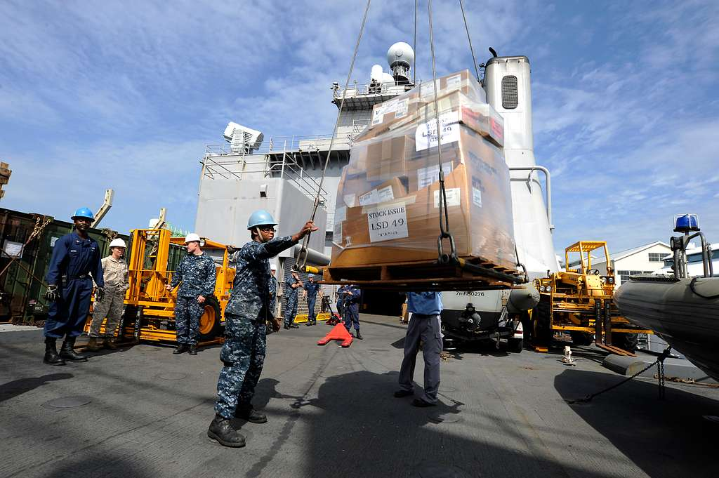 Seaman Rachel Mackey guides a pallet of stores as it is craned aboard USS Harpers Ferry (LSD 49)..