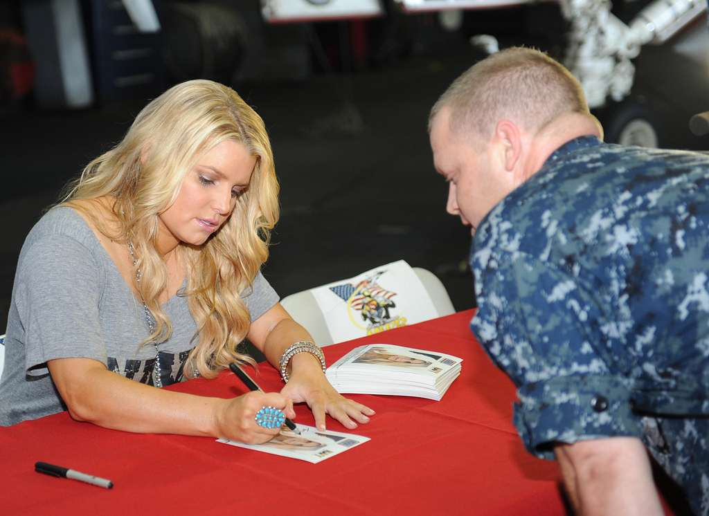 Jessica Simpson autographs a photo for a Sailor during a USO and Navy Entertainment sponsored visit aboard USS Harry S. Truman (CVN 75).