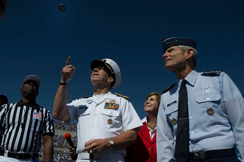 Chairman of the Joint Chiefs of Staff Adm. Mike Mullen, his wife, Deborah Mullen, and Gen. Norton A. Schwartz participate in the coin toss prior to kickoff of the U.S. Air Force Academy Falcons versus the U.S Naval Academy Midshipmen football game.