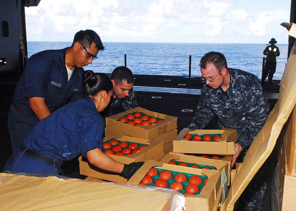Sailors move tomatoes aboard USS Essex (LHD 2) during a replenishment at sea.