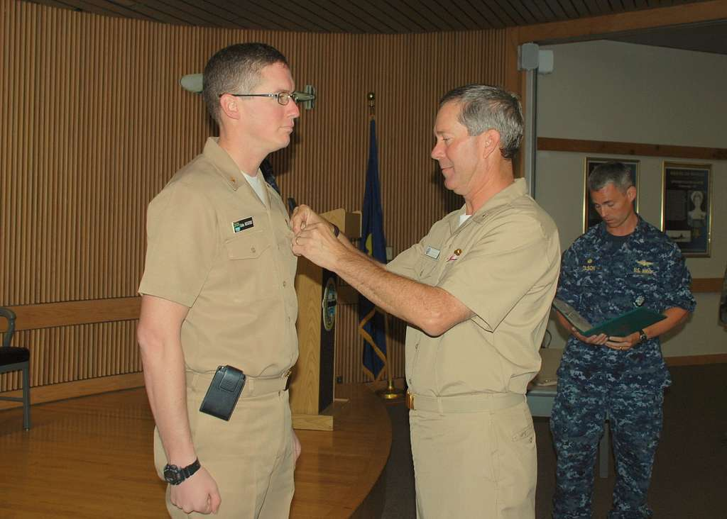 Rear Adm. Michael McLaughlin, right, pins the Bronze Star Medal on Lt. Cmdr. Colin McGuire in Bledsoe Hall at Navy Submarine School.