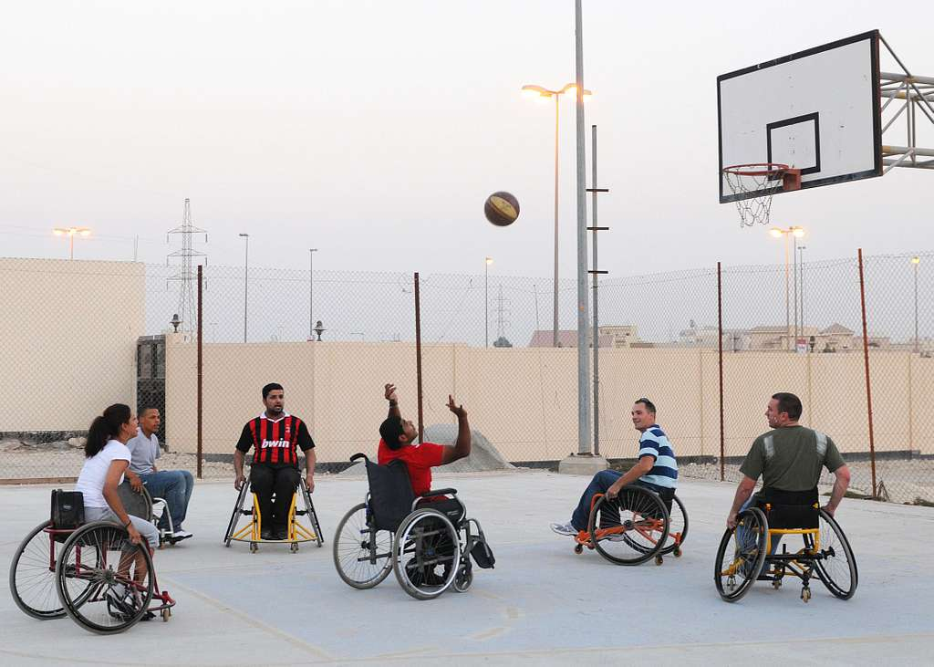 Sailors assigned to the amphibious dock landing ship USS Carter Hall (LSD 50) play wheelchair basketball with residents of the Bahrain Mobility Institute during a community service project.