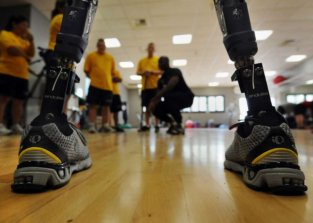 Navy volunteers are framed between the prosthetic legs of a Paralympic Military Sports Camp participant at Balboa Naval Medical Center.