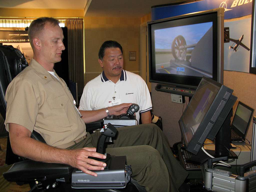 System Engineer Larry Nakamura, from Boeing Training Systems Group, instructs Maj. Christian Ward,