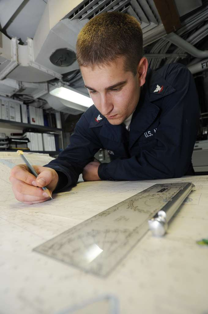 Quartermaster 3rd Class Benjamin Pinon, from Miami, charts the ship's course in the chart room aboard the aircraft carrier USS Harry S. Truman (CVN 75).