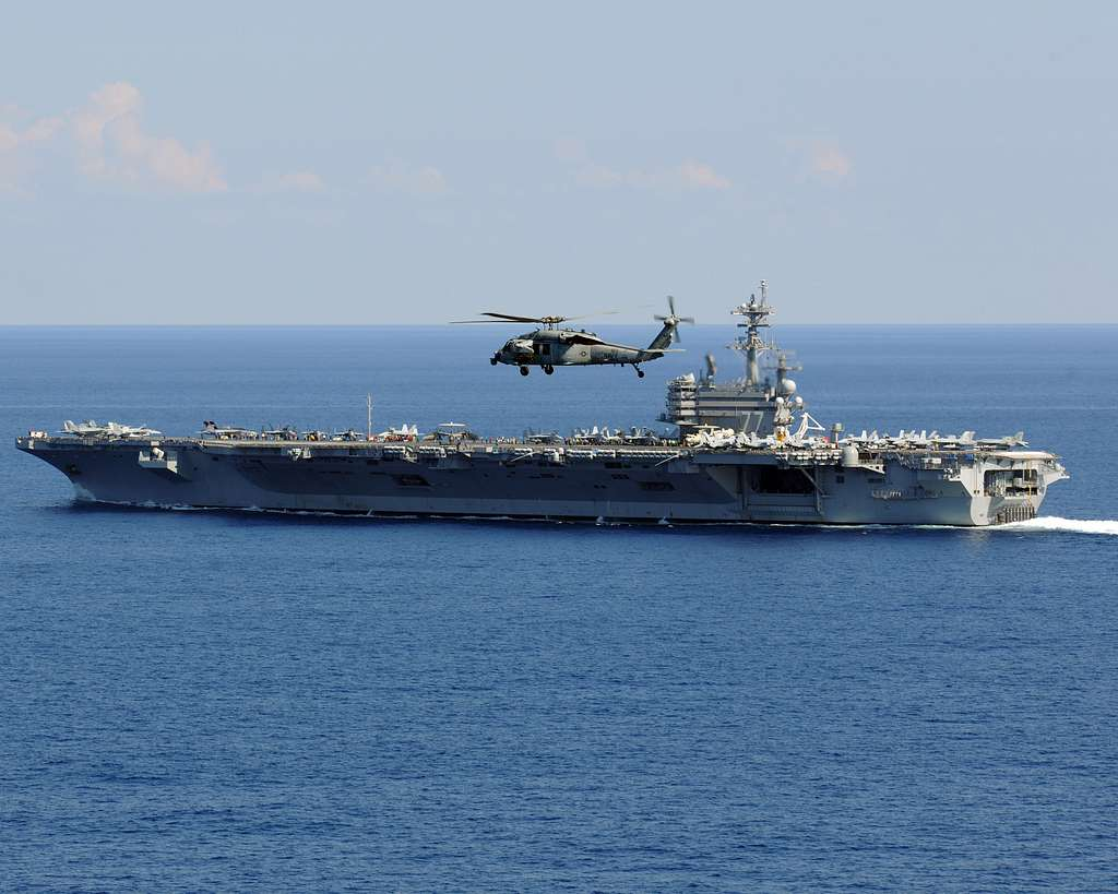An MH-60S Seahawk helicopter assigned to Helicopter Sea Combat Squadron (HSC) 9 flies over the aircraft carrier USS George H.W. Bush (CVN 77).