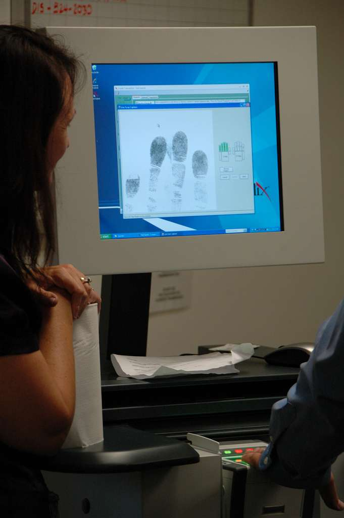 Mary Strand, a security specialist at  Fleet and Industrial Supply Center (FISC) San Diego, watches a demonstration of the digital fingerprint system.