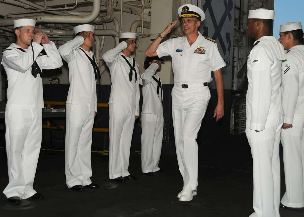 Rear Adm. Ron Horton, commander of Logistics Group Western Pacific, passes through sideboys aboard the forward-deployed amphibious assault ship USS Essex (LHD 2).