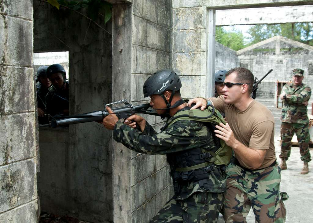 U.S. Navy Master-at-Arms 2nd Class Ryan Wehrsig demonstrates the second-man position in room-clearing procedures to Armed Forces of the Philippines special forces candidates during vessel boarding search and seizure training.