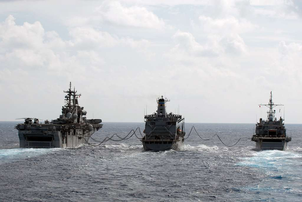 The Military Sealift Command fleet replenishment oiler USNS Pecos (T-AO 197), center, refuels the amphibious assault ship USS Essex (LHD 2), left, and the amphibious transport dock ship USS Denver (LPD 9).