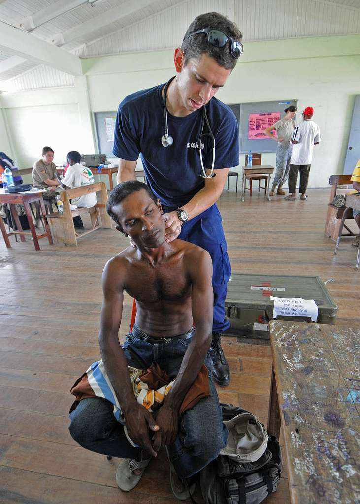Lt. j.g. Jeff McCroskey examines a man for a collarbone injury during a Continuing Promise 2010 medical civic action program in Orealla, Guyana.