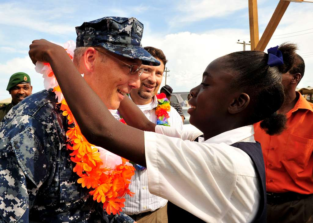 Capt. Thomas Negus, commodore of Continuing Promise 2010, receives a lei from a girl during a ceremony closing the Guyana phase of the Continuing Promise 2010 mission.