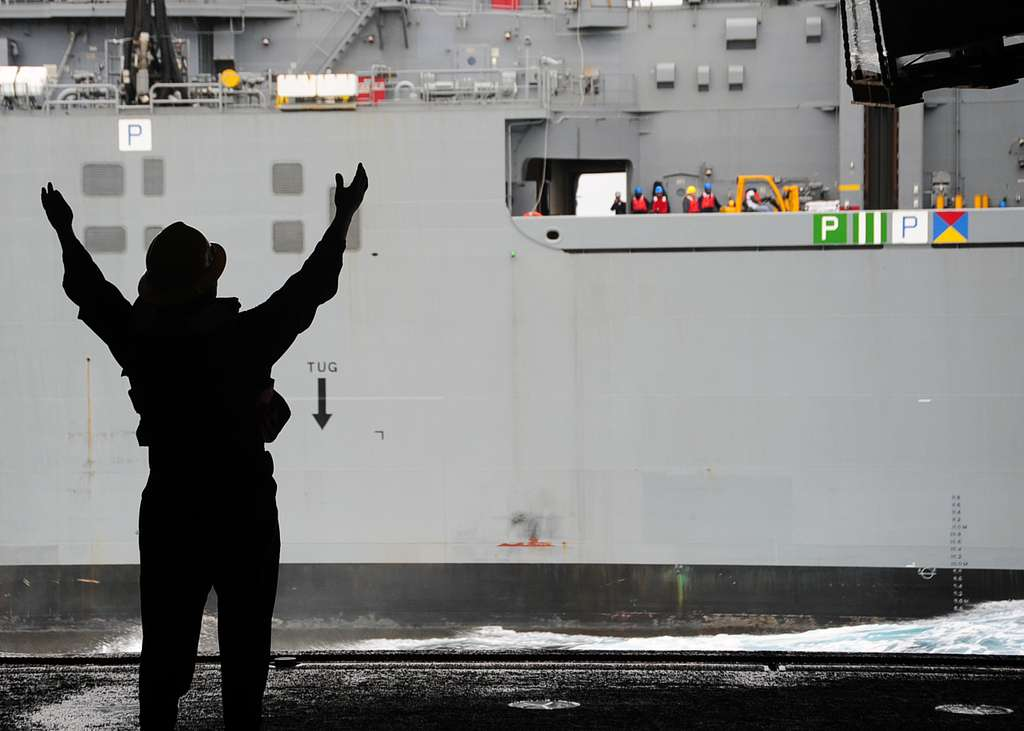Boatswain's Mate 2nd Class Justin Brewer, from Tulsa, Okla., signals from the aircraft carrier USS George Washington (CVN 73) to the Military Sealift Command dry cargo and ammunition ship USS Carl Brashear (T-AKE 7).