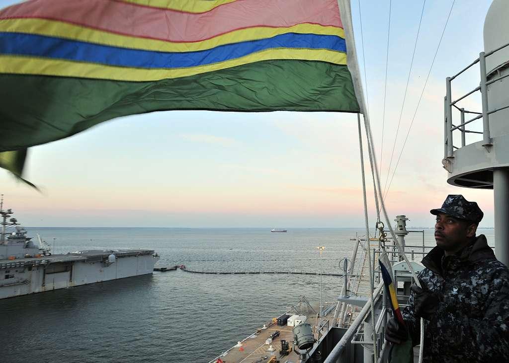 Quartermaster 2nd Class William C. Jerman raises award pennants at sunrise aboard the aircraft carrier USS Enterprise (CVN 65).
