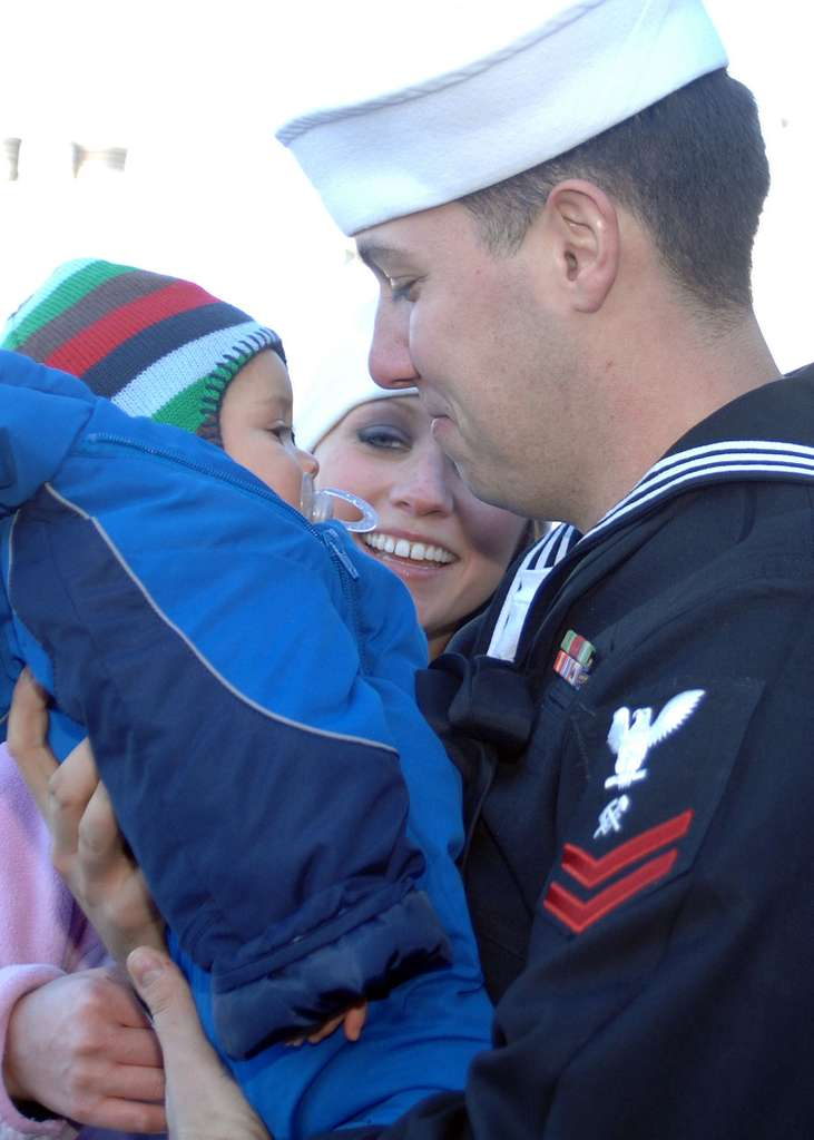 Hull Maintenance Technician 2nd Class Woren Walken greets his wife and seven-month-old son during a homecoming celebration for the guided-missile frigate USS Kauffman (FFG 59).