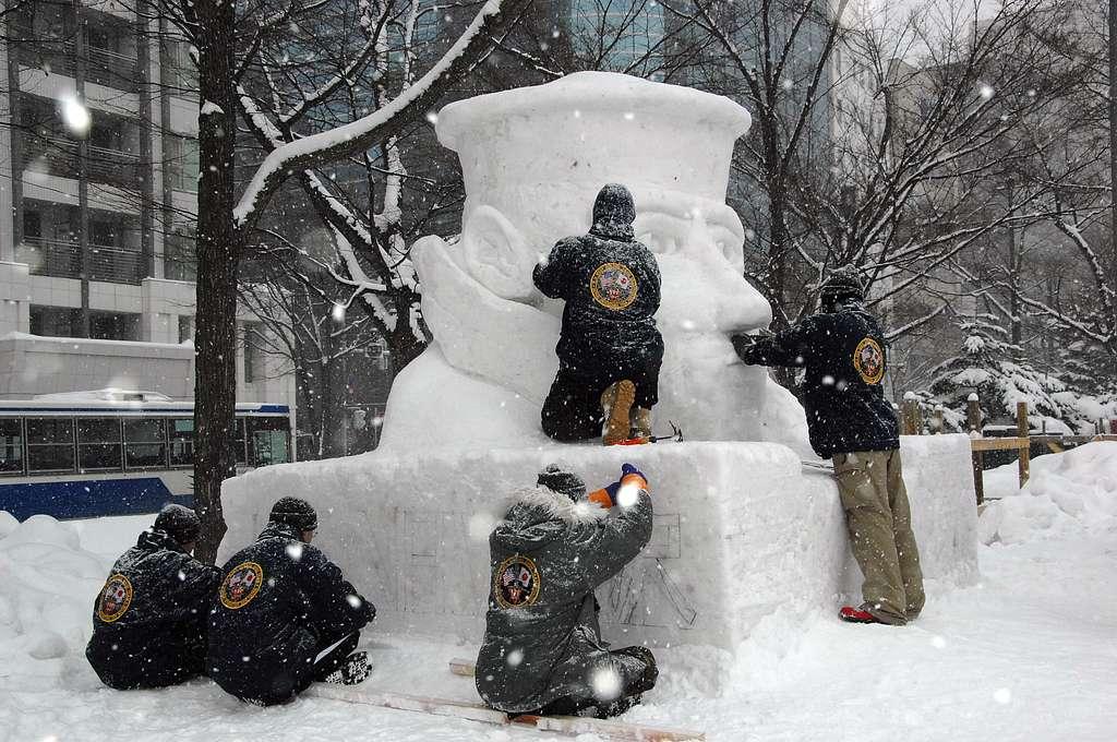 The Navy Misawa snow sculpture team sculpts a snow bust of