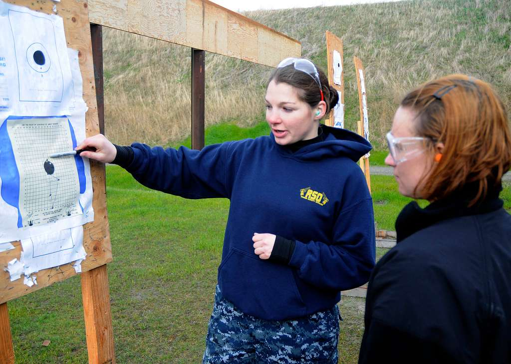 A Sailor gives feedback on another Sailors shooting during a live-fire training exercise as part of the Auxiliary Security Force training course.