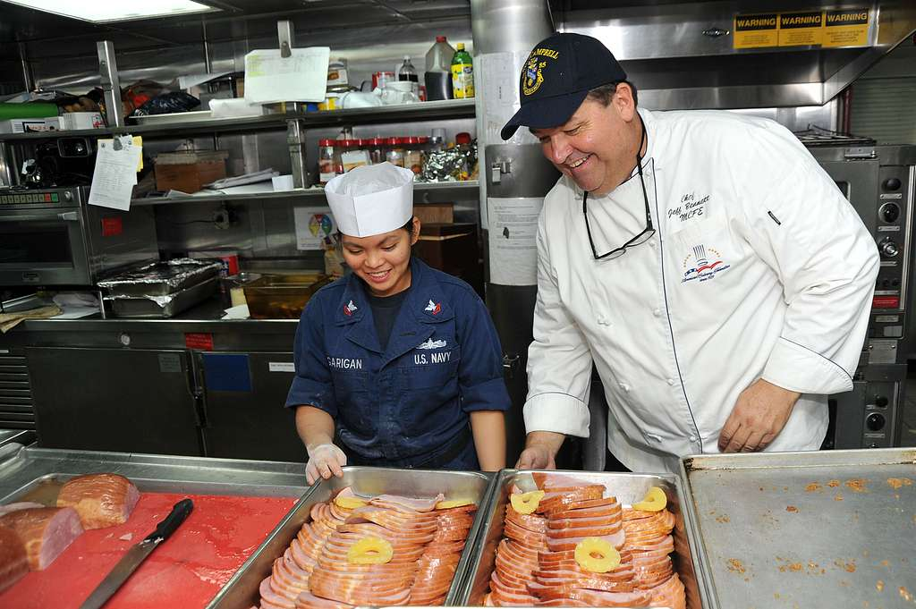 Executive Chef Jeff Bennett assists Culinary Specialist 2nd Class Ferose Pagarigan prepare a meal aboard the Arleigh Burke-class guided-missile destroyer USS McCampbell (DDG 85).