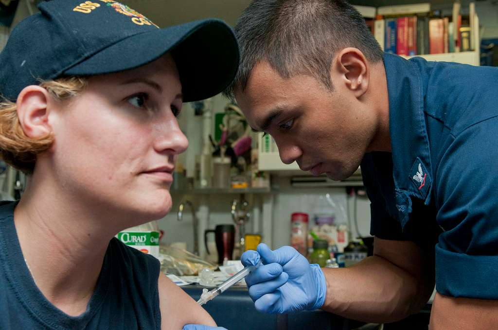 Hospital Corpsman 3rd Class Franz Malitig gives an influenza vaccine shot  to Electricians Mate 2nd Class Olivia Cannon aboard the guided-missile  cruiser USS Hue City (CG 66). - PICRYL Public Domain Search