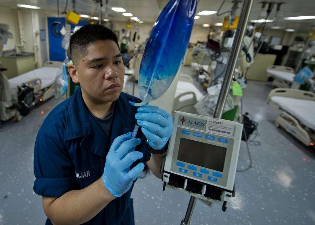 Hospitalman Reyhan Viajar injects methylene blue vein stainer into an IV bag in the intensive care unit aboard the amphibious assault ship USS Bonhomme Richard (LHD 6).