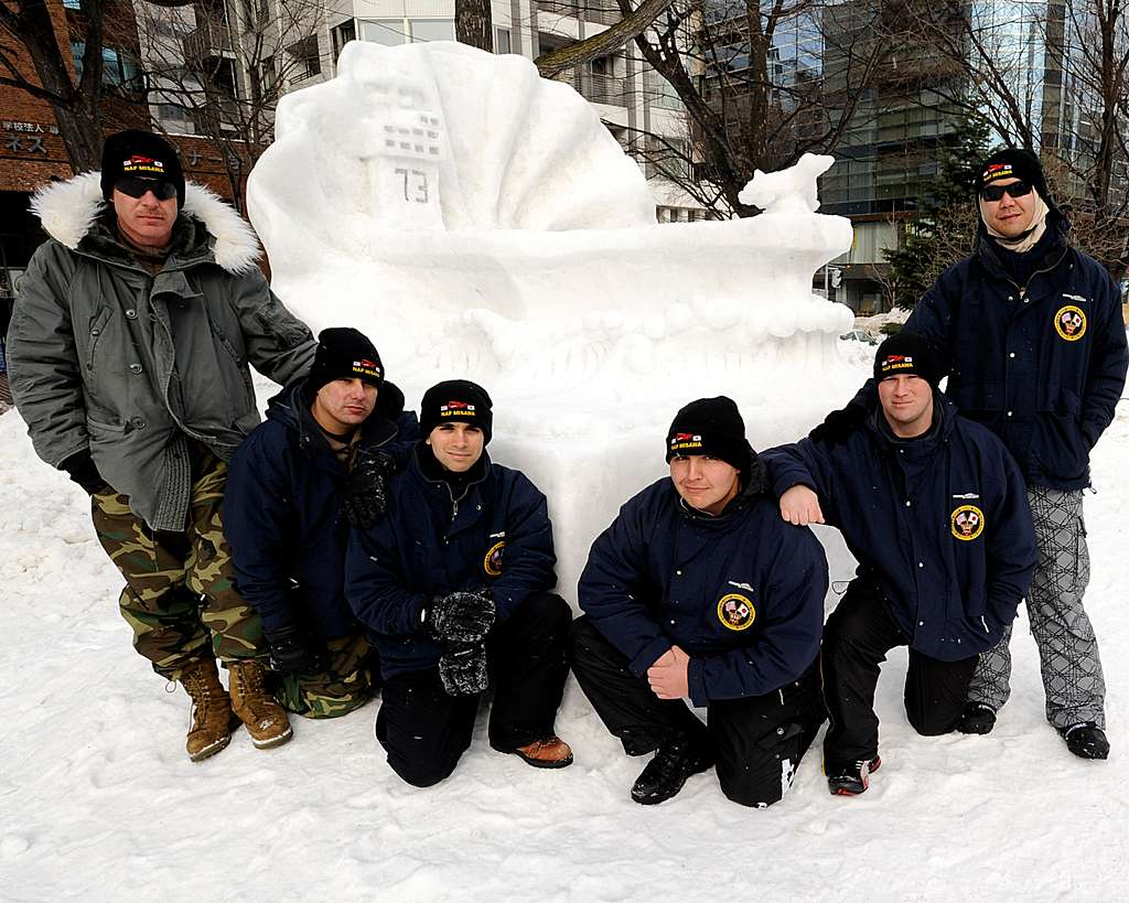 The Navy Misawa Snow Team gathers in front of their snow sculpture of the aircraft carrier USS George Washington (CVN 73).