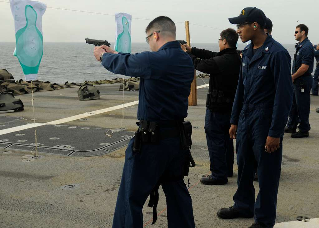 Sailors fire 9 mm pistols during a live-fire exercise on the flight deck aboard the amphibious command ship USS Blue Ridge (LCC 19), U.S. 7th Fleet flagship.