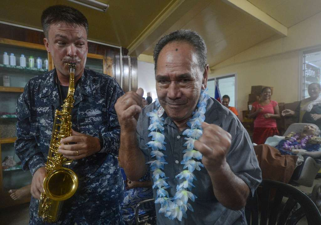 A U.S. Pacific Fleet Band member entertains a resident of Little Sisters of the Poor nursing home while visiting to donate medical supplies and bedding during Pacific Partnership 2013.