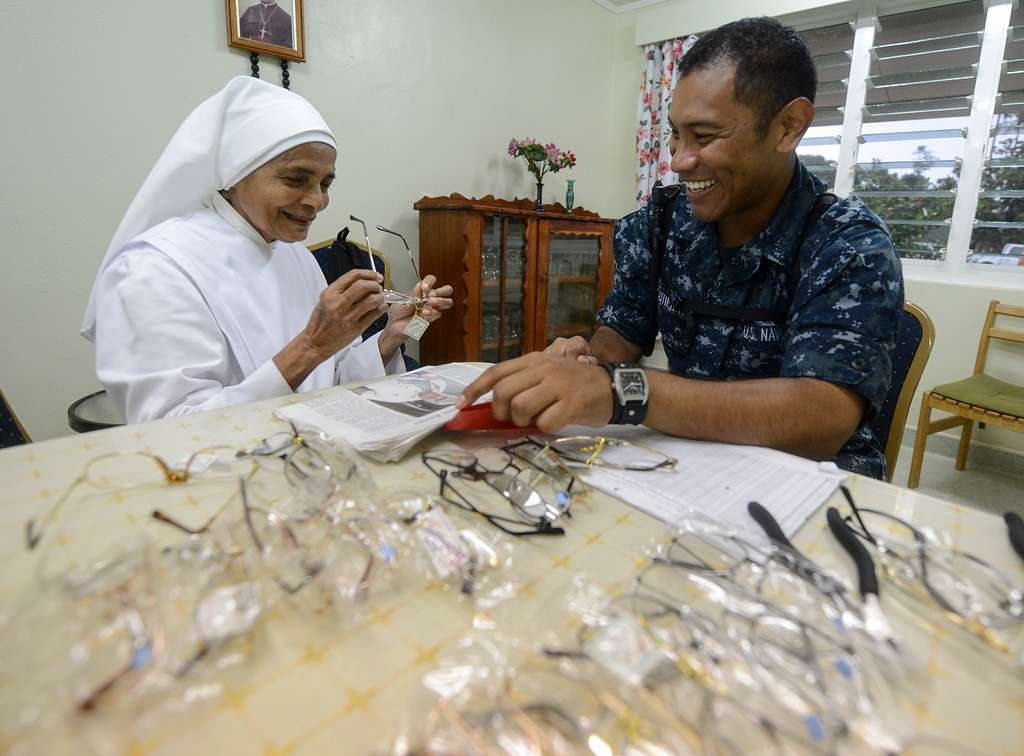 U.S. Navy Hospital Corpsman Herber Gutierrez prescribes a pair of reading glasses to Sister Margaret Du Coeur Immaculee of Little Sisters of the Poor nursing home while visiting to donate medical supplies