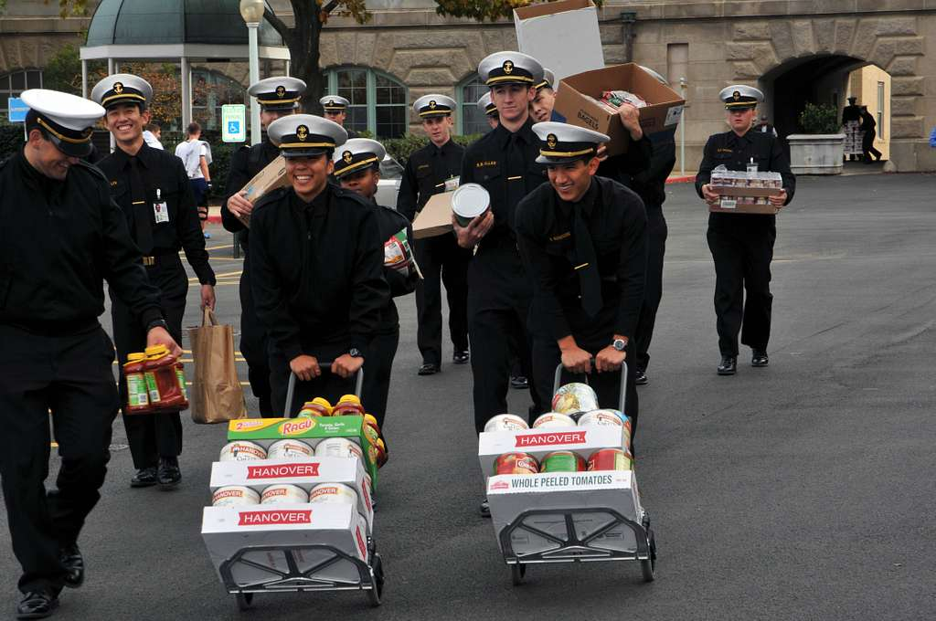 Midshipmen deliver nonperishable food to the parking lot of the Midshipmen Store for the Harvest for the Hungry food drive onload at the U.S. Naval Academy.