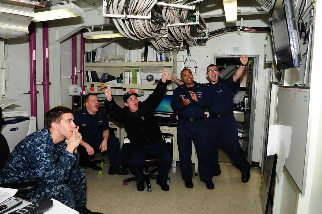 Sailors from the aircraft carrier USS Theodore Roosevelt (CVN 71) cheer on the Navy during the Army vs. Navy football game.