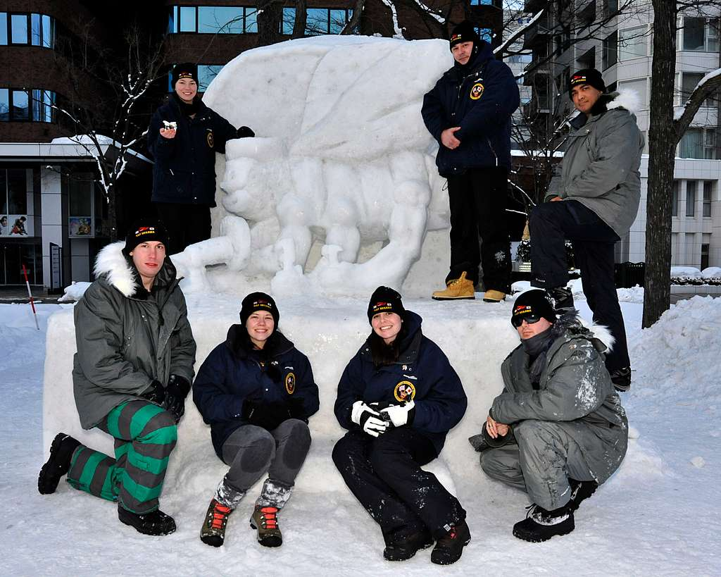 The 2014 Navy Misawa Snow Team poses with their snow sculpture after completing their second day of building.