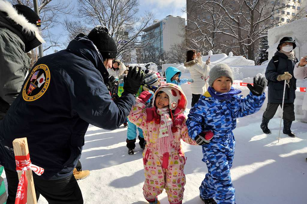 Sailor gives a high-five to a small child during the 65th Annual Sapporo Snow Festival.