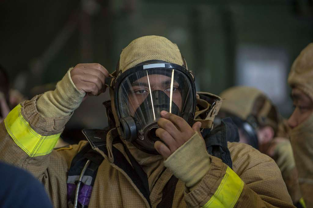 A Sailor dons a self-contained breathing apparatus mask during a general quarters drill aboard the amphibious assault ship USS Boxer (LHD 4).
