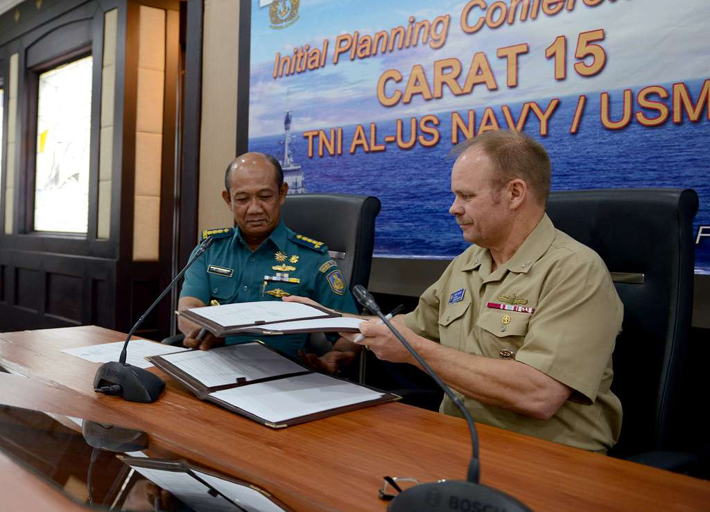 Col. Laut M. Zaenal, left, and Capt. Curtis Gilbert, assigned to Commander Task Force 73, exchange the official minutes of the Cooperation Afloat Readiness and Training (CARAT) Indonesia initial planning conference.