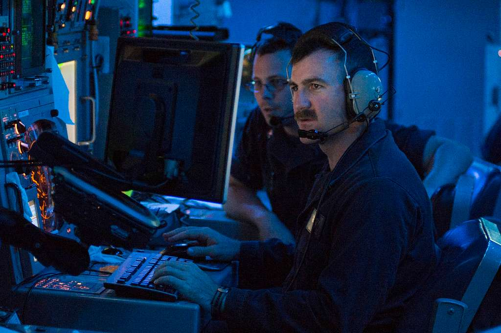 Lt. j. g. Carson Talley and Fire Controlman 3rd Class Mark Sieczkowski participate in an in-position operating exercise in the combat information center aboard the guided-missile destroyer USS Laboon (DDG 58) with Romanian sailors.