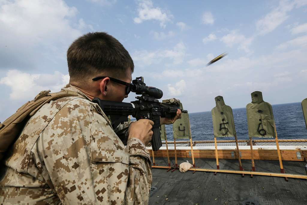 U.S. Marine Lance Cpl. Kenneth Klee fires an infantry automatic rifle during a deck shoot aboard the USS Anchorage (LPD 23).