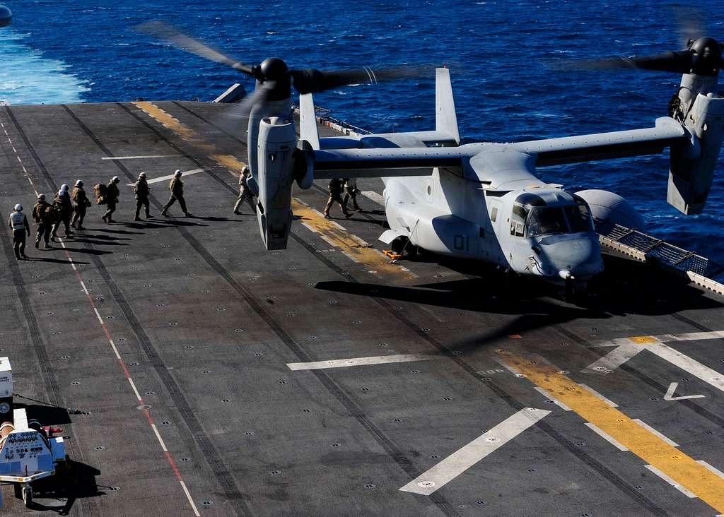 Marines board a MV-22 Osprey on the flight deck of amphibious assault ship USS Boxer (LHD 4).