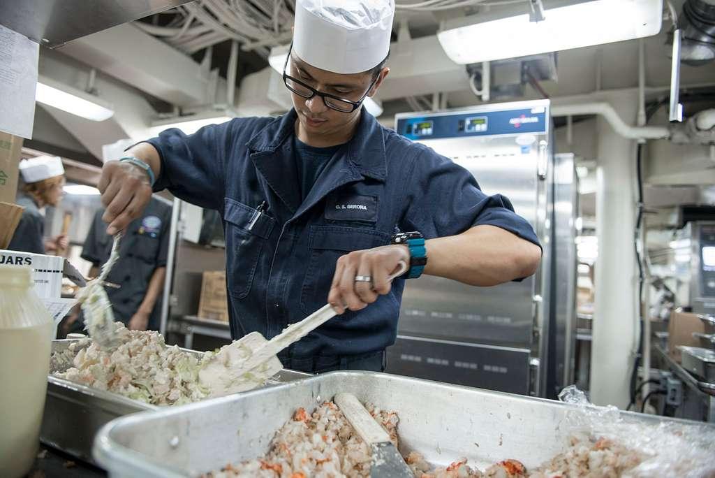 Culinary Specialist Seaman Daniel Gerona, from Garden Grove, California prepares coleslaw for Thanksgiving dinner aboard the U.S. Navy's only forward-deployed aircraft carrier USS Ronald Reagan (CVN 76).