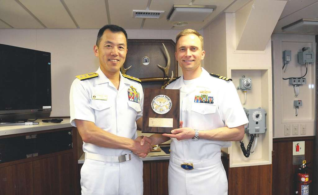 Japan Maritime Self-Defense Force (JMSDF) Rear Admiral Hiroshi Ito and U.S. Navy Commander Edward D. Sundberg hold a plaque celebrating the partnership between both forces in preparation for the annual bilateral Guam Exercise (GUAMEX).
