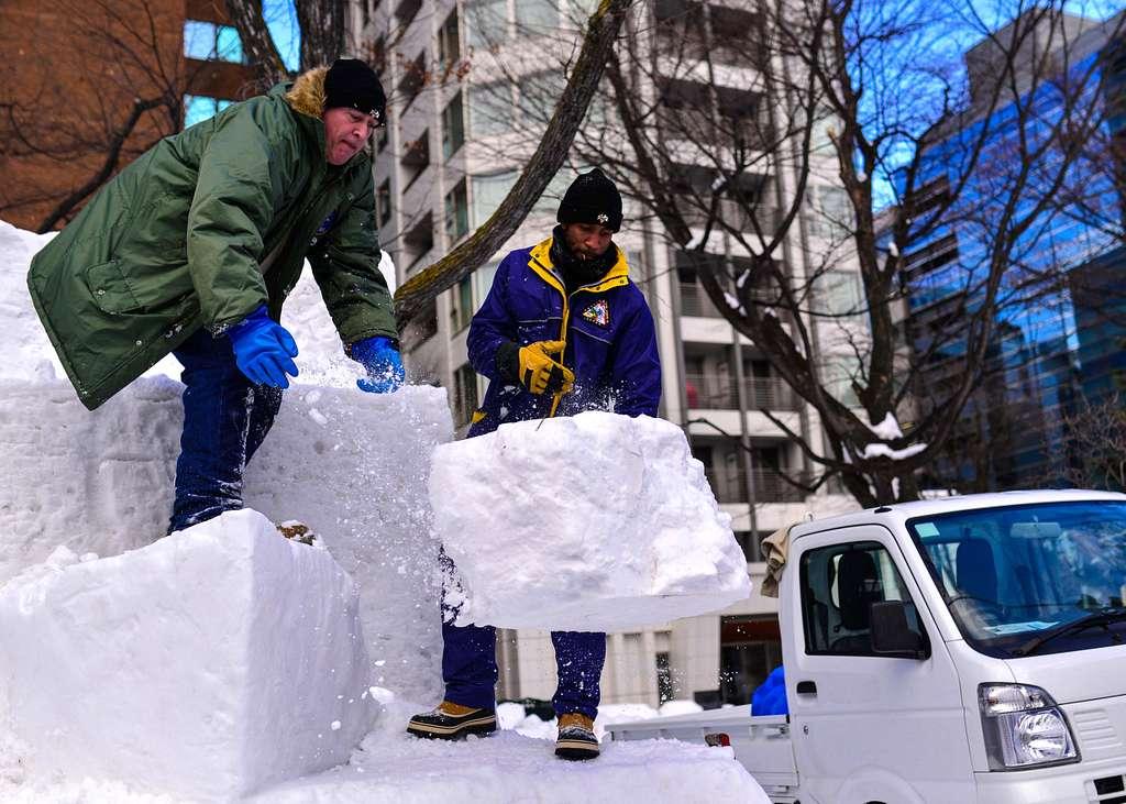 Sailors shape a 10 feet by 10 feet three-dimensional surface warfare pin snow sculpture in preparation for the 67th Annual Sapporo Snow Festival.
